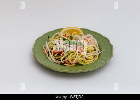 Healthy imitation noodles made with spiralized zucchini, decorated with basil leaves and a slice of lemon, on green plate, isolated on white backgroun - Stock Photo