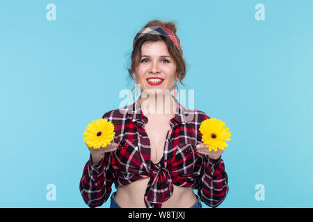 Gerberas, pin-up and fun concept - cheerful young woman with flowers in retro style on blue background - Stock Photo