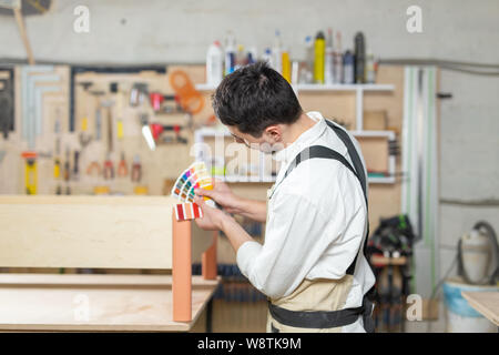 Small-Sized Companies, furniture and worker concept - Handsome young man working in the furniture factory - Stock Photo
