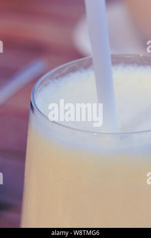 Close up delicious homemade milkshake with straw texture background. - Stock Photo