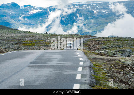Camper car in norwegian mountains. Tourism vacation and travel. Caravan car RV travels on the mountain road, pass Norway. Scandinavia Europe - Stock Photo