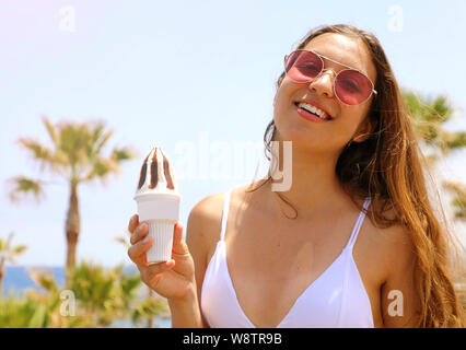 Girl eating ice cream on Tenerife beach with palm trees on the background - Stock Photo