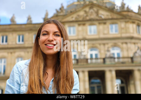 Smiling young woman in front of Neues Schloss (New Palace) of Stuttgart, Germany - Stock Photo