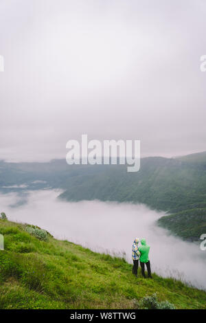 Hiking in Norway. Romantic couple of tourists on the edge of cliff looking on beautiful scenery. Back view of couple hugging at observation deck with - Stock Photo