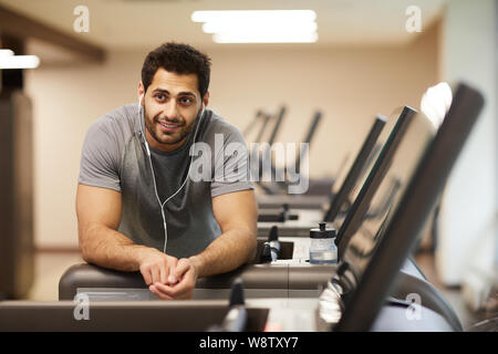 Portrait of muscular man taking break from workout in gym and listening to music, copy space