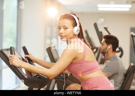 Waist up portrait of young woman wearing headphones looking at camera while exercising in gym, copy space - Stock Photo