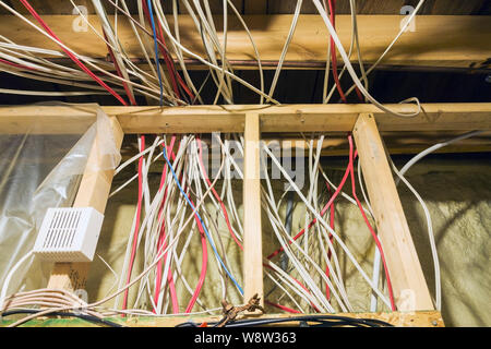 Exposed wiring in opened stud wall with yellow foam insulation in utility room in basement inside a residential home - Stock Photo
