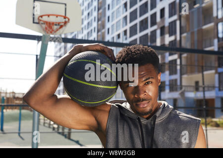 Portrait of handsome African-American man holding basketball ball looking at camera while posing in sports court outdoors, copy space