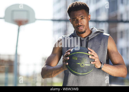 Waist up portrait of muscular African man holding basketball ball in outdoor court and looking at camera, copy space