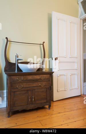 Antique oak wood vanity with bowl sink in water closet with stained white pine floorboards inside an old 1900 Victorian Queen Anne revival style house - Stock Photo