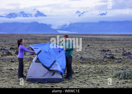 Tent - people pitching tent on Iceland at dusk. Couple setting up camp for night after hiking in the wild Icelandic nature landscape. Multicultural Asian woman and Caucasian man healthy lifestyle. - Stock Photo