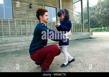 This handout still of the movie, Dad, Where Are We Going? , shows former Chinese Olympic diving champion Tian Liang and his daughter Cindy Tian Yuchen - Stock Photo