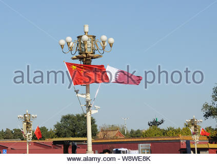 Chinese and Qatari national flags flutter on lampposts in front of the Tiananmen Rostrum during the visit of Qatar's Emir Sheikh Tamim bin Hamad al-Th - Stock Photo