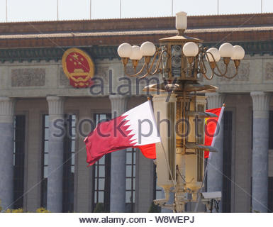 Chinese and Qatari national flags flutter on a lamppost on the Tiananmen Square during the visit of Qatar's Emir Sheikh Tamim bin Hamad al-Thani in Be - Stock Photo