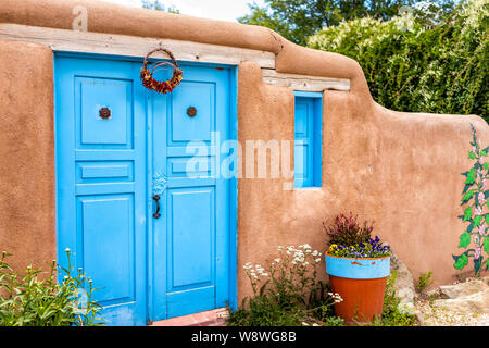 Ranchos de Taos, USA - June 19, 2019: Famous St Francic Plaza in New Mexico with turquoise adobe architecture color decorations on door - Stock Photo
