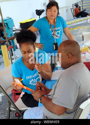 Orlando, United States. 11th Aug, 2019. Karen McKenzie (seated L) and Alvina Chu (standing) of the Orange County, Florida Health Department host a hepatitis A vaccination event in response to the hepatitis A outbreak in the State of Florida and the August 1, 2019 declaration of a public health emergency in the state. As of July 1, 2019, twenty-seven states have experienced outbreaks of the disease, with Florida having 2,586 reported cases, the third highest in the United States, resulting in 31 deaths. Credit: SOPA Images Limited/Alamy Live News - Stock Photo