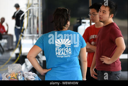 Orlando, United States. 11th Aug, 2019. Alvina Chu of the Orange County, Florida Health Department offers services to people at a hepatitis A vaccination event being held in response to the hepatitis A outbreak in the State of Florida and the August 1, 2019 declaration of a public health emergency in the state. As of July 1, 2019, twenty-seven states have experienced outbreaks of the disease, with Florida having 2,586 reported cases, the third highest in the United States, resulting in 31 deaths. Credit: SOPA Images Limited/Alamy Live News - Stock Photo
