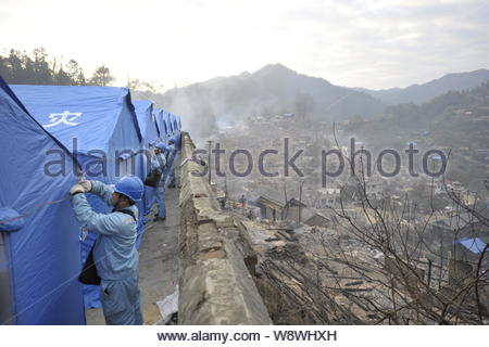 Chinese rescuers put up tents for villagers whose houses were devastated in a fire at a temporary settlement in Jiuji village of Miao ethnic minority, - Stock Photo