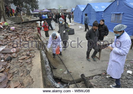 Chinese medical workers work in front of tents for villagers whose houses were devastated in a fire at a temporary settlement in Jiuji village of Miao - Stock Photo