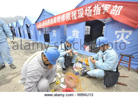 Chinese rescuers work in front of tents for villagers whose houses were devastated in a fire at a temporary settlement in Jiuji village of Miao ethnic - Stock Photo