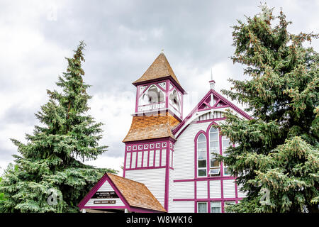 Crested Butte, USA - June 21, 2019: Colorado village Union Congregational Church in downtown in summer with tower and pink with white color on cloudy - Stock Photo