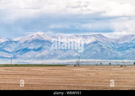 Route 285 in Colorado with rural countryside brown farm near Monte Vista and view of Rocky Mountains with water sprayer - Stock Photo