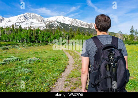 Thomas Lakes Hike with man looking at snow view of Mt Sopris, Carbondale, Colorado and meadow field and hiking trail road path - Stock Photo
