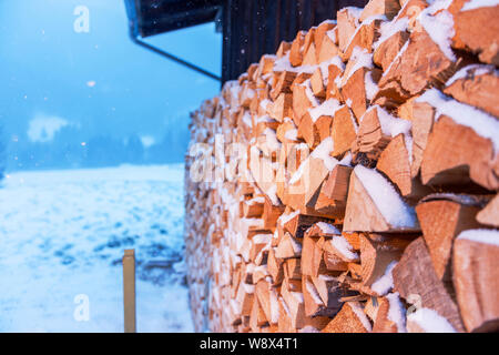 Full-sized side view of freshly beaten, stacked on a barn and snow-covered firewood in snowfall. - Stock Photo