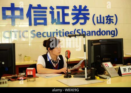 --FILE--A Chinese employee works at a branch of Citic Securities in Qingdao city, east Chinas Shandong province, 30 June 2014.   KKR is teaming up wit - Stock Photo