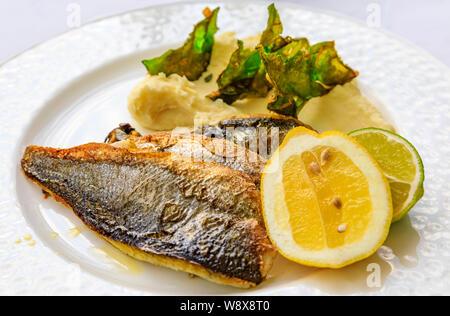 Pan seared branzino or sea bass served with lemon and lime wedges, and mashed potatoes with fried kale chips at an al fresco restaurant in Montenegro - Stock Photo