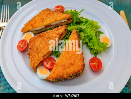 Fried sandwich, fritter, with goat cheese and Njeguski prsut cured meat served with tomatoes, boiled quail egg and salad, traditional Montenegrin food - Stock Photo