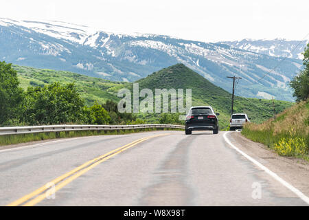 Aspen, USA - June 29, 2019: Brush Creek road street to Snowmass Village, Colorado town with cars in traffic and mountain range - Stock Photo