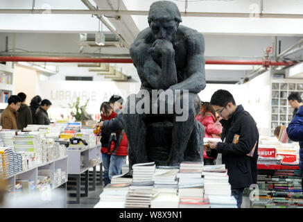 --FILE--Customers read or shop for books next to a replica of The Thinker at the Librairie Avant-Garde bookstore in Nanjing city, east Chinas Jiangsu - Stock Photo