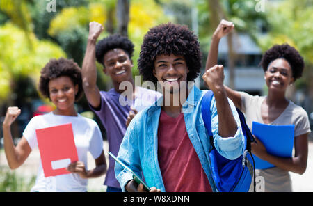 Cheering african american university student with group of african american students outdoor in the summer - Stock Photo