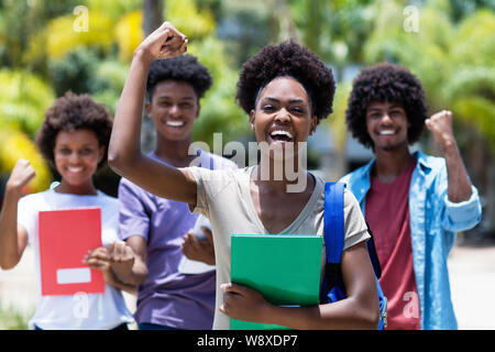 Cheering african female student with group of african american students outdoor in the summer - Stock Photo
