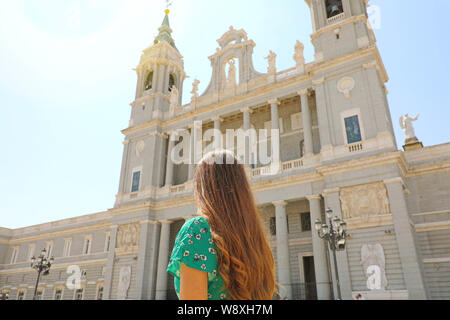 Back view of young woman in Madrid with Almudena Cathedral on the background, Spain - Stock Photo