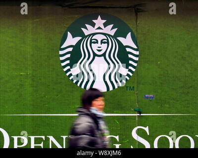 --FILE--A pedestrian walks past advertisement for Starbucks Coffee in Shanghai, China, 20 February 2013.   A toxic food scandal in China is spreading - Stock Photo