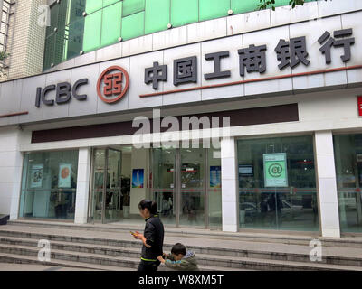 --FILE--Pedestrians walk past a branch of ICBC (Industrial and Commercial Bank of China) in Chongqing, China, 20 July 2014.    The Industrial and Comm - Stock Photo