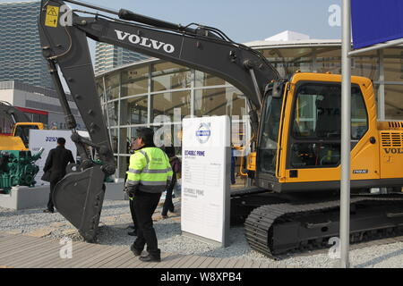 --FILE--A Chinese employee walks past a Volvo excavator manufactured by Volvo Construction Equipment during the 2010 International Trade Fair for Cons - Stock Photo