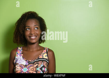 Beautiful african american woman looking sideways to a green wall