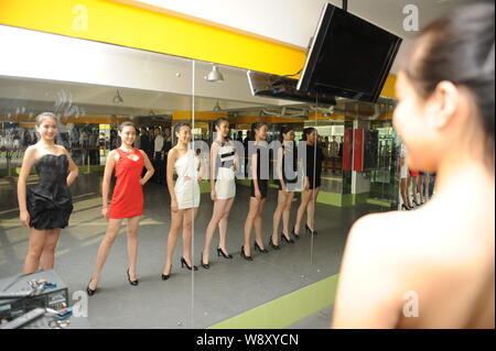 Young female Chinese students pose in front of a mirror during a model training session at an art school in Weifang city, east China's Shandong provin - Stock Photo