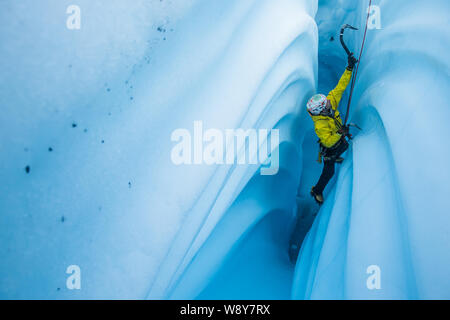 Ice climber ascending a narrow passage inside a glacier ice cave with wavy lines from melting ice cutting into the walls. - Stock Photo