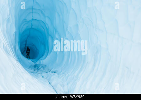 A young woman wanders into the depths of a huge ice cave inside a glacier in Alaska. - Stock Photo