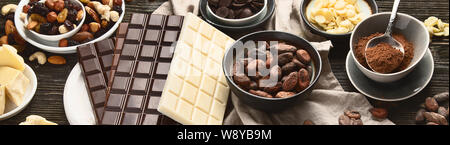 Dark bitter, milk and white chocolate,  cocoa butter, cacao powder and beans on wooden table. Top view. Panorama, banner - Stock Photo