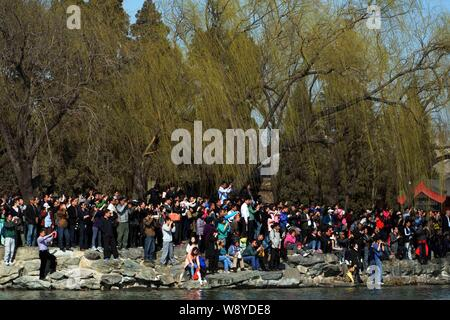 Tourists crowd the bank of Kunming Lake as they look at or take photos of U.S. first lady Michelle Obama, her daughters and mother, accompanied by new - Stock Photo