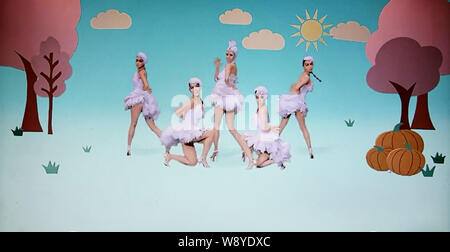 In this screenshot taken on 17 November 2014, Chinese pop singer Wang Rong and dancers, dressed in chicken costumes, are flapping their arms like cluc - Stock Photo