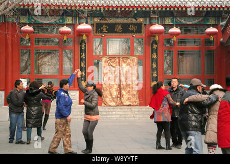 People dance in front of the closed Imperial Court Club, also known as Yushantang operated by high-end restaurant chain Yi Shi Liu, at Beihai Park in - Stock Photo