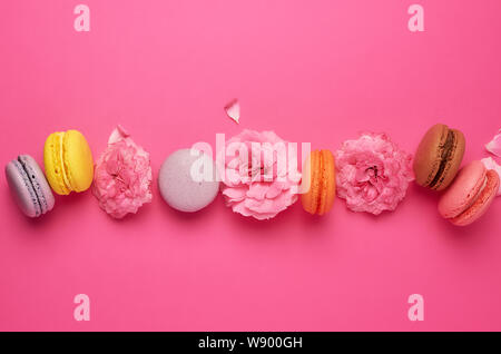 sweet multi-colored macarons with cream and a pink rose bud with scattered petals on a pink background, top view, flat lay, copy space - Stock Photo