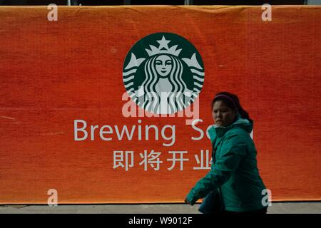 --FILE--A pedestrian walks past advertisement for Starbucks Coffee in Shanghai, China, 21 February 2014.   A toxic food scandal in China is spreading - Stock Photo