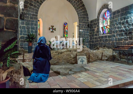 Tabgha, Israel - May 18 2019: Nun praying in the Church of the multiplication of the loaves and fishes in Tabgha, Israel - Stock Photo